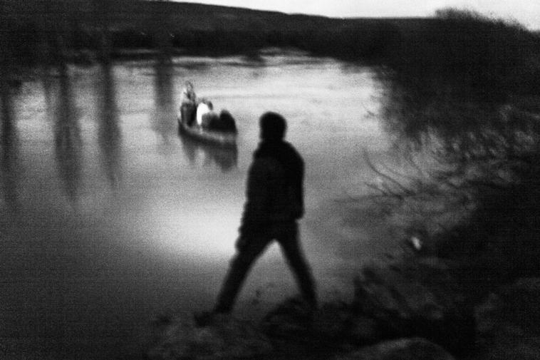 Bild: TURKEY. March 2, 2012. Along the Turkish-Syrian border in Hatay Province. Under the cover of night a network of Syrian smugglers transport a family fleeing the violence inside Syria on a rowboat across the Orentes River, which marks a stretch of the border between northern Syria and southern Turkey.