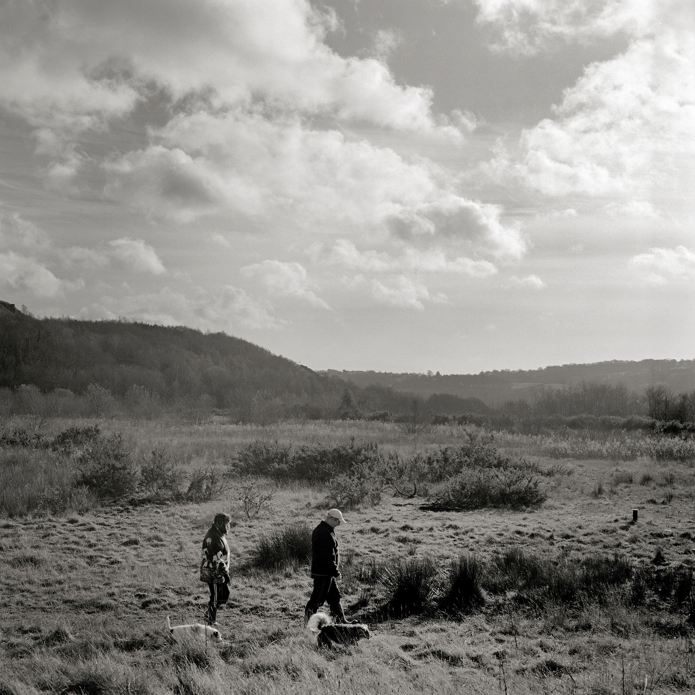 Bild: Einwohner von Ynysybwl, Wales, wandern mit ihren Hunden über das Gelände des früheren Lady Windsor Bergwerks, das 1988 geschlossen wurde. Davon ist nichts mehr übrig. Foto: Kaveh Rostamkhani