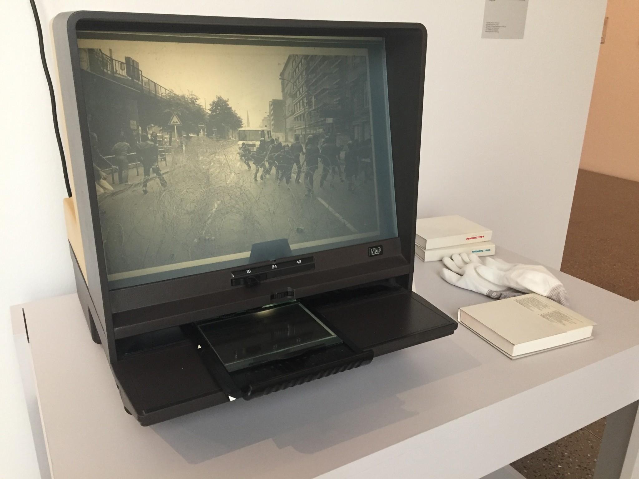 Microfiche-Lesegerät mit der Arbeit Fotonetz. Auf dem Monitor ein Foto von Kurt Schrage zur Anti Reagan Demo in Berlin. Ausstellungsfoto: Peter Liedtke
